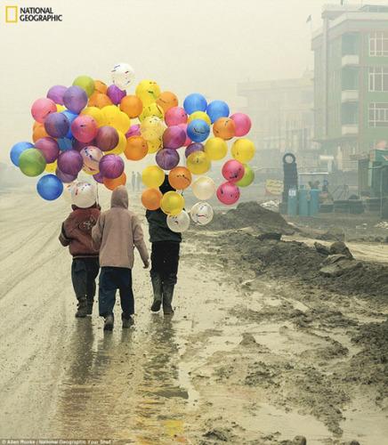 喀布尔的气球:阿伦・鲁克在阿富汗首都参加世界粮食计划署的一个冬季行动的时候,在街头拍到了这张照片。他说,男孩们手中的彩色气球组成了他那一天的颜色。