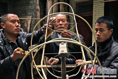 """家住施秉县城沙河街七十多岁的老先生田应祥(中)是""""亮龙""""的传人,每年农历正月是他忙碌的日子,这是他带着两个儿子在扎""""龙头""""。.jpg"""