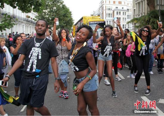 """8月24日,一年一度的""""诺丁山狂欢节""""在伦敦开幕,伦敦西区方圆数公里的区域变成一片欢乐的海洋。""""诺丁山狂欢节""""以非洲和加勒比地区文化为主题,是欧洲规模最大的街头文化艺术盛会,也是英国多元文化的象征之一,从1964年开始举办,每年都吸引上百万世界各地游客参加。中新社发 周兆军 摄"""