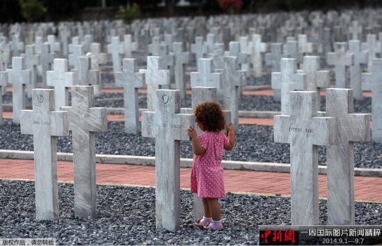 9月4日,希腊Zeitelnik墓地,一名儿童站在墓碑旁。当日,希腊等国举行一战百年纪念活动。