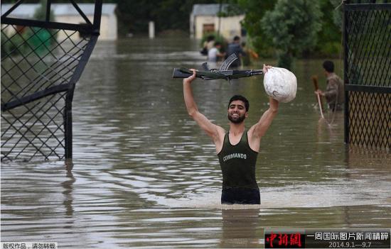 9月4日,印度斯利那加郊区,一名印度警察在遭遇洪水的街道中举着武器前行。