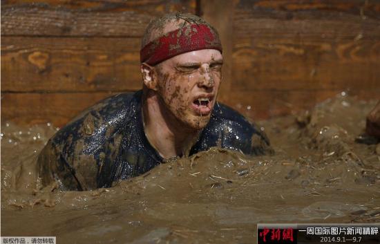 9月6日,德国阿恩斯贝格,民众参加泥巴硬汉比赛耐力项目比拼,在泥浆中翻越障碍,争夺冠军。