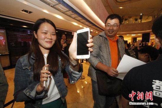 图为:2014年10月17日零点,江苏省南京市,iphone6开卖。市民到场排队购买,现场买到手机的市民笑开颜。图片来源:CFP视觉中国