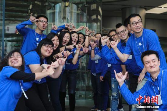 """10月17日,在北京王府井苹果专卖店店内员工摆出数字""""6""""和""""+""""的手势迎接顾客。当日,iPhone 6及iPhone 6 Plus在中国内地市场正式发售。 中新社发 熊然 摄"""