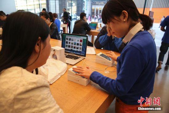 10月17日,在北京华贸苹果专卖店店内店员正在给顾客激活和测试手机。当日,iPhone 6及iPhone 6 Plus在中国内地市场正式发售。 中新社发 熊然 摄