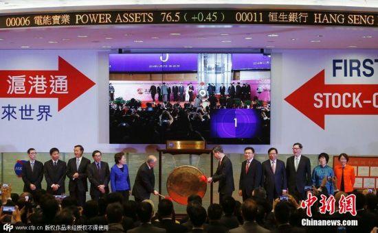 11月17日,香港特区行政长官梁振英(中右)和香港交易所主席周松岗(中左)在香港交易所一起敲锣,宣布沪港通正式开通。图片来源:CFP视觉中国