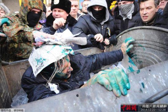 当地时间2014年12月24日,乌克兰哈尔科夫,示威者在当地议会大厦外集会,要求市长Gennady Kernes辞职,并与警方发生冲突,示威者将市议会代表扔进垃圾桶里。