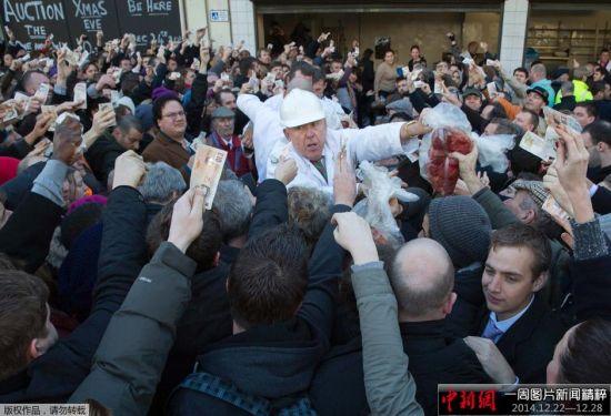 当地时间2014年12月24日,英国伦敦,圣诞节前一天,史密斯菲尔德市场进行年度圣诞拍卖,人们争抢鲜肉。