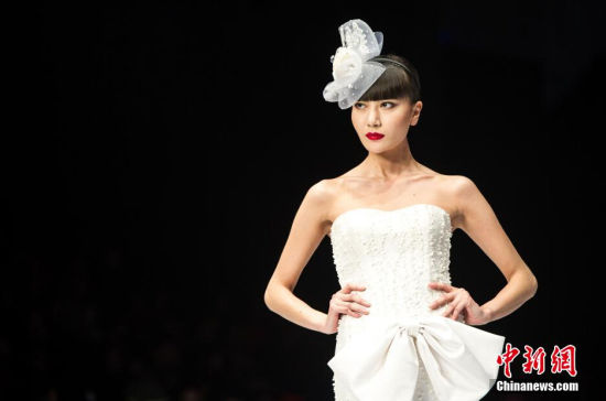 1月3日晚,马来西亚国宝级设计师、明星御用设计师、CarvenAcademy时尚学院院长Carven ONG带领他的梦幻婚纱礼服,压轴亮相首届中国—东盟国际时装周。图为模特穿着婚纱礼服走秀。 中新社发 洪坚鹏 摄