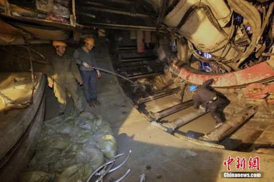 2014年12月31日晚,天津地铁6号线施工隧道最深处,老夏对施工质量极为苛刻,亲自与劳务农民工一同清除管片泥土。 张道正 摄