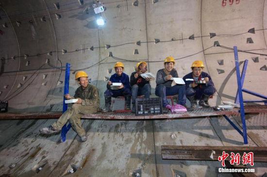 """2014年12月31日晚,天津地铁6号线施工隧道最深处,劳务农民工在吃饭。由于是新年夜,饭菜也加了一些""""硬""""货。一位劳务农民工说虽然工作辛苦点,但吃的还不错,旁边另一位劳务农民工说,你就是一个吃货。说完,逗得大家哈哈大笑。 张道正 摄"""