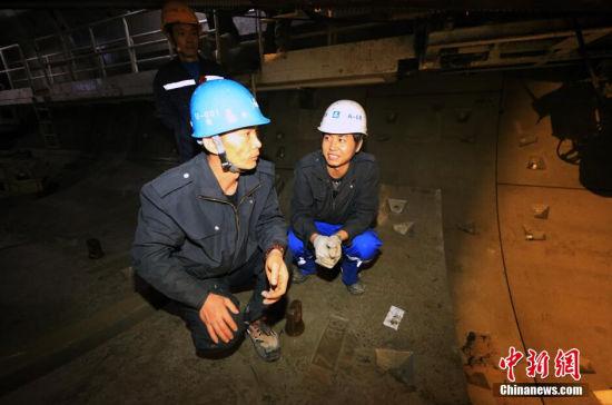 2014年12月31日晚,天津地铁6号线施工隧道最深处,老夏正在给他的徒弟讲解盾构拼装时需要注意的事项。 张道正 摄