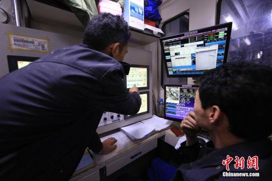 2015年1月1日凌晨,新年钟声早已敲响,天津地铁6号线施工隧道最深处,老夏和盾构操作手依然监控着盾构掘进的相关数据。 张道正 摄