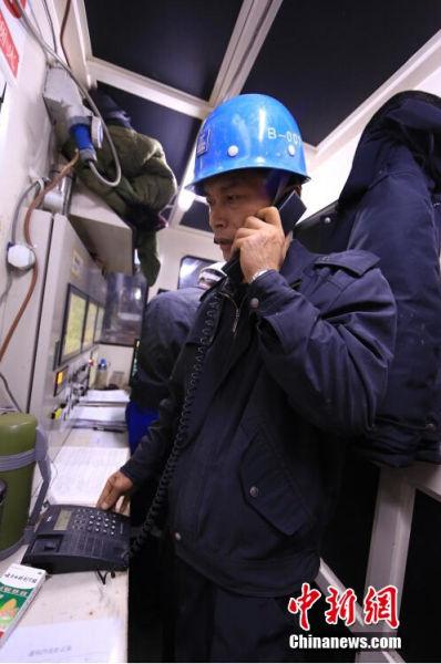 2014年12月31日晚,天津地铁6号线施工隧道最深处的盾构机里,现场气温已经达到27度,老夏脱下外套,用内部电话询问龙门吊的维修情况。张道正 摄