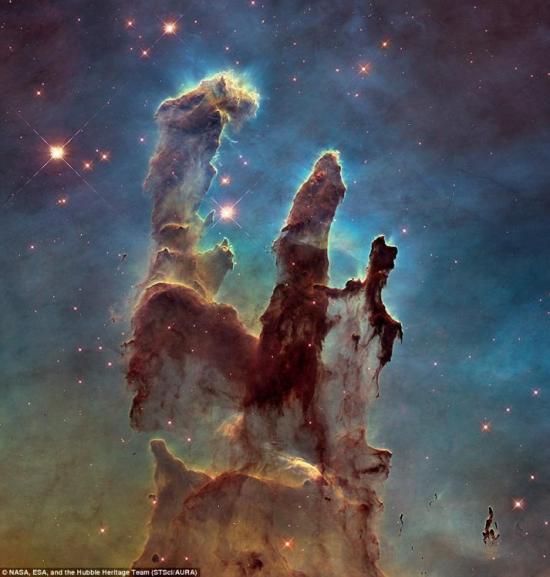 """据英国《每日邮报》1月5日报道,为了庆祝象征性的""""创造之柱""""(Pillars of Creation)照片拍摄二十周年,美国国家航空航天局(NASA)利用哈勃太空望远镜重新捕获了这些柱子,其详细程度简直令人叹为观止。哈勃太空望远镜对这些柱子拍摄了一张新的、更大的、更高分辨率的图片,这张新的图片与哈勃太空望远镜拍摄到的其他几个图片结合起来创造了这些柱子迄今为止最好的景观图。(网页截图)"""