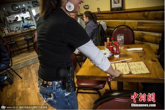 """当地时间2014年1月5日,美国科罗拉多州的赖夫尔(Rifle)小镇上,一家名为""""Shooters""""的餐馆,店如其名,所有服务员都配枪服务。尽管这里的法律规定,在公共场所持枪属于违法行为。2013年该餐馆开业才一个月,就有一男子在外被杀,于是老板让所有员工,服务员,厨师,全员配枪,并且员工都参加过武器培训。"""