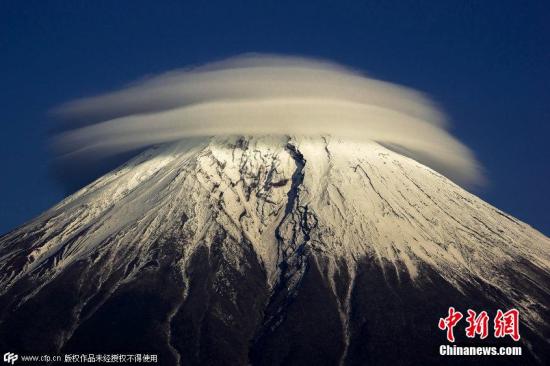 2015年1月19日报道,日本富士山,在晴朗的一天,神奇的云层在富士山山顶形成了一个奇特的环形形状,这是由于潮湿气流在高纬度遇到了例如山脉或者建筑这样的障碍物,阻断了气流的流通,随着空气中水分的凝结,下风侧形成了这样的奇特景观。图片来源:CFP视觉中国