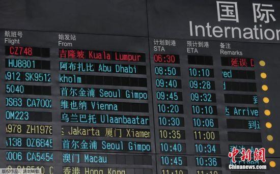 """时间回到2014年3月8日,马来西亚航空公司B777-200ER型飞机(机身编号9M-MRO),执行MH370(吉隆坡至北京)航班任务,起飞时间8日00:42(北京时间)。01:20飞机在胡志明管制区同管制部门失去通讯联络,同时失去雷达信号,经向相关管制部门联络证实,该机一直未与我国管制部门建立联络或进入我国空管情报区。该航班共有239人,其中中国人154名,外国人73名,机组员工12名。航班原计划6:30在北京降落。从吉隆坡飞往北京途中失去联系。图为2014年3月8日,北京首都国际机场内屏幕显示关于MH370航班飞机""""延误""""的消息(红字)。"""