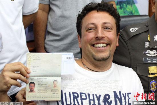 随后一则关于两名冒用失窃护照的乘客的消息引起了各方的高度关注并由此引发了关于MH370被恐怖分子劫持猜测,马航失踪的原因变得越来越破朔迷离。图为泰国普吉岛,意大利男子Luigi Maraldi在由泰警方举行的新闻发布会上展示自己现在的护照。据悉,他原先的护照于2013年8月1日在泰国被盗,其曾回意大利重新办理护照后返回泰国。