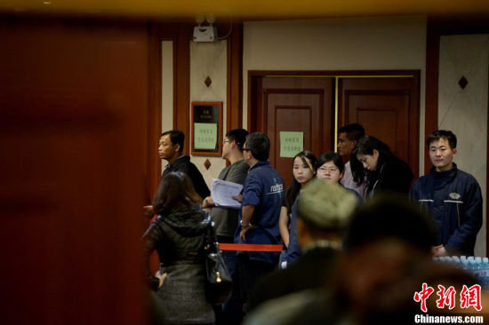 2014年3月12日,北京,马航履行慰问金承诺,向失联家属发放3.1万元人民币现金,现场秩序井然。图为站在门口负责安排发放抚慰金的马航工作人员正在念名单。 图片来源:CFP视觉中国