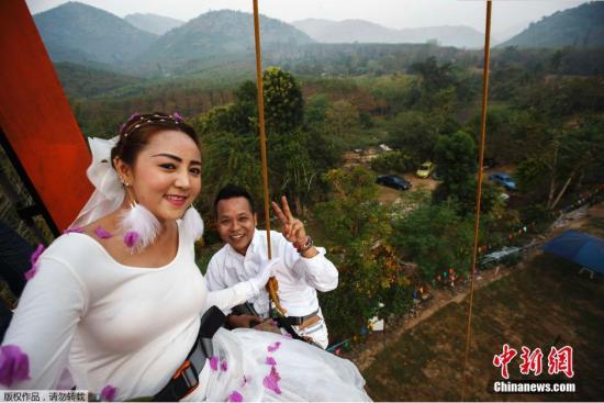 当地时间2015年2月13日,泰国武里府,情人节将至,泰国三对新婚夫妻参加了一个度假村举办的寻找快乐主题的婚礼仪式,体验与羊群赛跑,从3.5米高蛋糕雕塑跳下,以及攀爬高墙等活动。