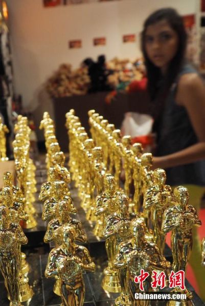 """2月16日,洛杉矶好莱坞大道杜比剧院前封闭道路,开始为22日第87届奥斯卡颁奖典礼搭建观礼台、铺设红毯。杜比剧院附近商家的奥斯卡""""小金人""""也因此收到更多游客的青睐。中新社发 毛建军 摄"""
