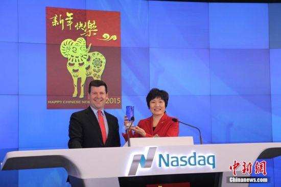 美国东部时间2月18日,中国驻纽约总领事章启月大使敲响纳斯达克开市钟,喜迎新年。图为纳斯达克副总裁麦柯奕向首次到纳斯达克敲钟的章启月大使赠送礼物。中新社发 邓敏 摄