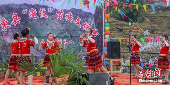 """2月26日,中国农历大年初八,世界遗产地贵州施秉县城关镇小河村在穿村而过的美丽小河河畔举行""""遨攸""""苗族文化节:搭在河水上的舞台交融在山水之间,摆在草坪上的长桌歌声绵绵。活动当天,虽然天气不佳,却阻挡不了人们前来聚会的热情。民族歌舞、长桌对歌、拔河、斗牛、斗鸡、斗鸟等活动让到场观众品尝到一场精彩的原生态苗族文化盛宴。中新社发 奉力 摄"""