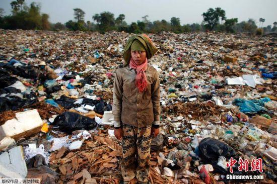 图为15岁的女孩Chan Thy正在垃圾堆中捡拾可用的物品。