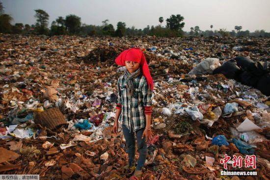 图为5岁的女孩Saven正在垃圾堆中捡拾可用的物品。