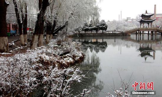 2015年4月4日,甘肃张掖普降大雪,气温下降到了零下2度,雪后的张掖城区银装素裹,各种树木像披上了迎春的彩衣,宛如美丽的童话世界,吸引清明小长假的市民走出家门踏雪赏景。图为瑞雪中的甘泉公园。中新社发 闫自伟 摄 图片来源:CNSPHOTO