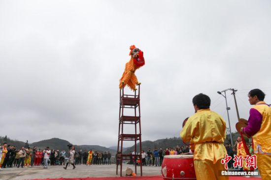 """2015年4月8日,一年一度的仡佬族裔祭天朝祖活动在贵州务川举行。每年的清明节前后,来自全国各地的仡佬族裔都会齐聚""""仡佬之源""""务川洪渡河畔,祭拜先祖。仡佬族祭天朝祖仪式,被列为""""国家优秀民族节庆"""",仪式包括礼祭、文祭、乐祭三部分。图为高台舞狮表演。贺俊怡 摄"""