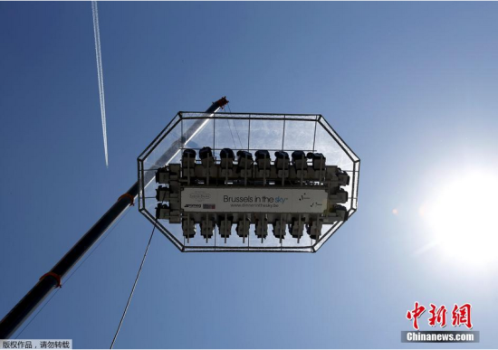 """6月7日消息,比利时布鲁塞尔,Cinquantenaire公园前悬挂起40米高餐厅,可供22人享受""""空中盛宴""""。"""