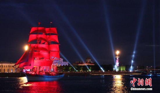 """6月20日,圣彼得堡中学毕业生们迎来了一年一度的""""红帆节""""。这一节日是为庆祝中学生顺利毕业,今后或将走进大学或将走向社会而设立。""""红帆""""一词取自一部描述年轻人之间爱情的苏联小说,象征着激情、梦想和幸福。在俄罗斯其他地方,""""红帆节""""又被称为""""中学生毕业日"""",各地都会举行庆祝活动。图为当晚凌晨时分,一艘驶挂着红帆的三桅大船在灯光和焰火的映衬下缓缓驶入人们的视线。中新社发 王修君 摄"""