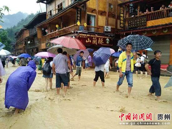 资料图:6月21日,西江千户苗寨景区遭受特大暴雨,游客在古街上行走。