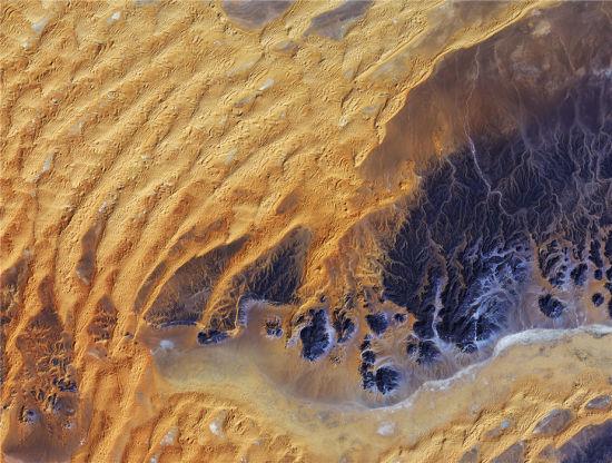 这一图像拍摄了阿尔及利亚的东南部,撒哈拉沙漠的心脏地带。由于炎热和缺水,沙漠地带并不适宜人类,因而卫星成为了对该区域进行大规模观察和监测的最佳方式。在太空中拍摄的沙漠,由于其多样性和原始性的状态,成为独特而引人注目的迷人图景。(图片来源:JAXA/ESA)