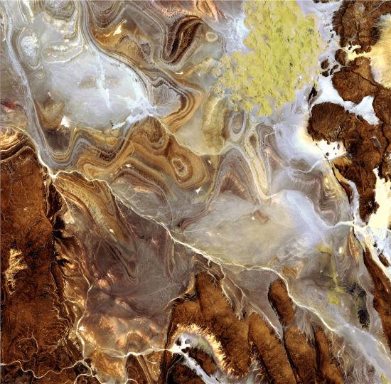 """塔奈兹鲁夫特盆地是撒哈拉沙漠最为荒凉的地区之一。由于缺乏水和植被,该盆地被称为""""恐怖之地"""",暗色的砂岩山丘,白色的岩滩,岩石高原等等,组成了这里的特色。该图片由日本的先进陆地观测卫星(ALOS)拍摄于2009年。(图片来源:JAXA, ESA)"""