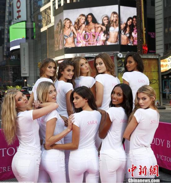 当地时间2015年7月28日,纽约时代广场,新入选的维秘天使超模在纽约时代广场拍照。十位超模身着白色紧身衣,勾勒出美好的曲线,面对镜头大抛电眼,性感十足。