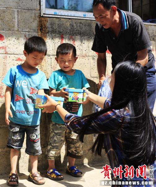 美籍华人文佳蕊向当地留守儿童赠送学习用品。