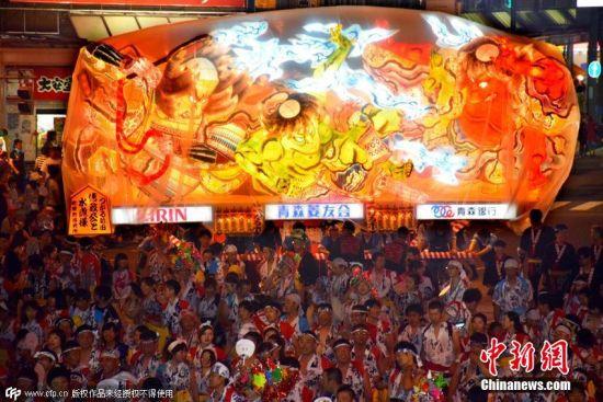 图为民众抬着大灯笼在街头游行。 图片来源:CFP视觉中国