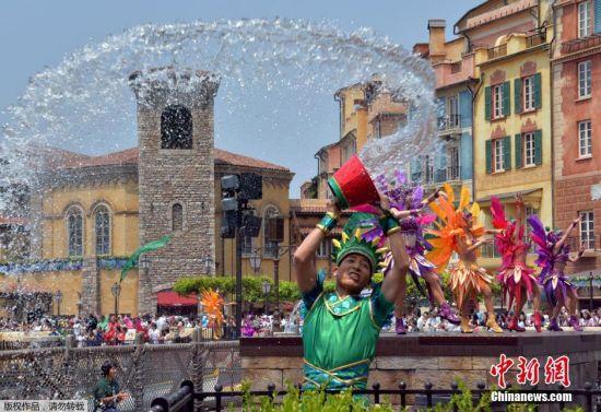 图为东京迪士尼内的工作人员将一桶水泼向空中。