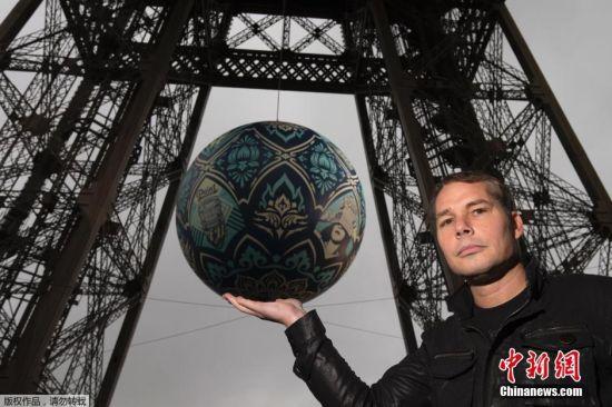 """11月23日,在法国巴黎,一个名为""""地球危机""""的大圆球悬挂在埃菲尔铁塔上。在巴黎气候变化大会开幕之前,美国艺术家谢泼德・费尔雷创作了一个名为""""地球危机""""的大圆球作品,经巴黎市政府和埃菲尔铁塔开发委员会许可将其悬挂在离地面60米高的铁塔二层之上。"""