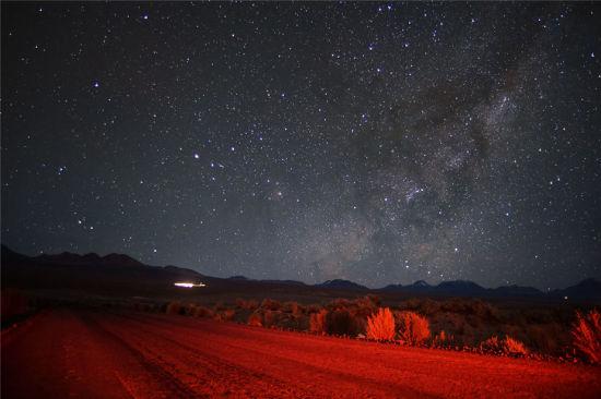 在漫天的星海中,银河系的光芒隐约可见,从阿塔卡马沙漠远处的山峰上升起。在前景中,沙漠公路和周围的植物被黯淡的红色灯光照耀。(图片来源:Carlos A. Durán/ESO)