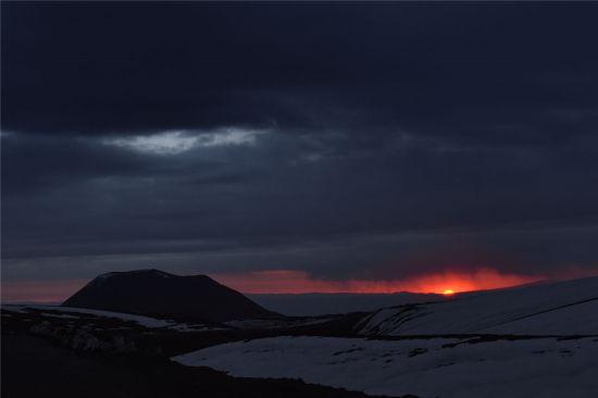 太阳炙热的光芒仍半遮面纱,夹在地平线与多云的暗沉天空之间。在前景中,冰雪覆盖的阿塔卡马沙漠,等待着再次拥抱太阳的光芒。(图片来源:Carlos A. Durán/ESO)