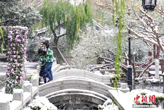 """济南迎来入冬首场降雪,趵突泉再现""""云蒸雾绕""""胜景。 中新社记者 张勇 摄"""