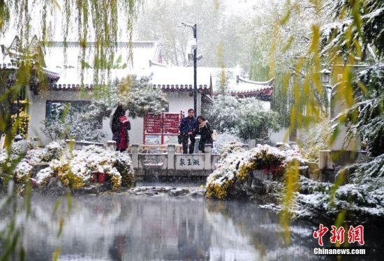"""一对恋人雪中观赏济南趵突泉""""云雾缭绕""""胜景。 中新社记者 张勇 摄"""