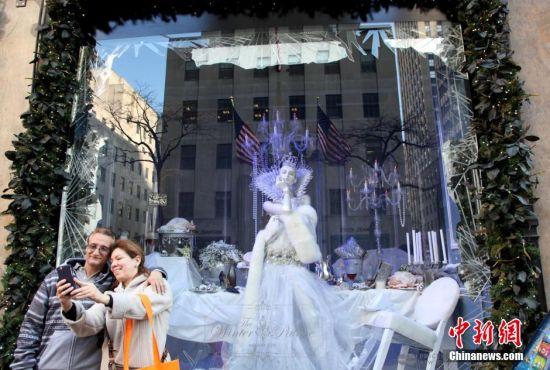 2015年圣诞临近,纽约曼哈顿第五大道著名的圣诞橱窗展梦幻登场,吸引了众多游客驻足欣赏。图为12月10日,当地民众在纽约曼哈顿第五大道一家百货公司橱窗前拍照。 中新社记者 阮煜琳 摄