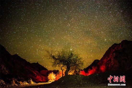 """12月9日深夜,晴空万里的国际旅游名城敦煌三危山上空出现繁星璀璨,宛如浩瀚外太空的神奇景象,令人叹为观止的美景吸引大批游客和摄影爱好者前来""""猎奇""""。""""三危""""是史书记载中最早的敦煌地名,这里自古以来都是敦煌一处重要的宗教胜地。东晋永和八年(352年),佛教徒开始在此创建洞窟。前秦建元二年(366年),高僧乐尊经此,见三危山状如千佛,始凿莫高窟。王斌银 摄"""