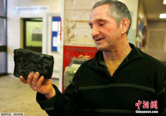 矿工Kevin McDonagh从自己最后一次挖出来的煤矿石上切割下一块,作为自己职业生涯的纪念。