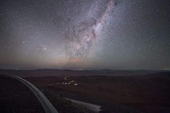 """欧洲南方天文台(ESO)的摄影师拍摄到了""""红色精灵""""的图片。""""红色精灵""""是在高海拔地区、出现在雷暴上空的一种罕见自然现象。在这张图像的中心,""""红色精灵""""的卷须似乎正在升起,抵达星光熠熠的夜空。(图片来源:P. Horálek/ESO)"""